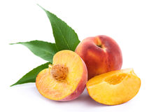 Fresh peach. Fruits with cut and green leaves isolated on white background royalty free stock photo
