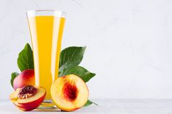 Fresh peach juice in elegance glass and ripe red nectarines with green leaves on soft white wood board, closeup. Sweet summer fruits and drinks royalty free stock images