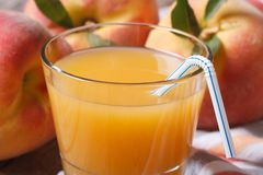 Fresh peach juice in glass closeup on a background of ripe fruit Royalty Free Stock Photos