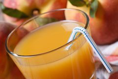 Fresh peach juice in glass macro on a background of ripe fruit Stock Photos