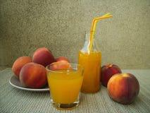 Fresh peach juice and ripe peaches, rustic set. stock image