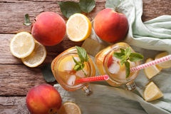 Fresh peach lemonade with ice and mint in a glass jar closeup. H Stock Images