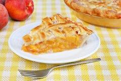 Fresh peach pie. One slice of fresh peach pie with a lattice top stock photo