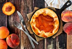 Fresh peach tart in cast iron skillet over rustic wood Royalty Free Stock Photography