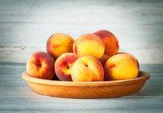 Fresh peach on wooden plate and board Royalty Free Stock Photography