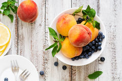Fresh peaches and blueberries in bowl on a light wooden background in rustic style. Top view Stock Images