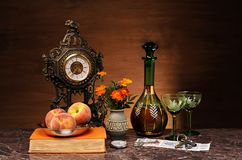 Fresh peaches, book, clock and flowers in a vase stock photo