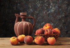 Fresh peaches and a ceramic pitcher. On the table Royalty Free Stock Photography