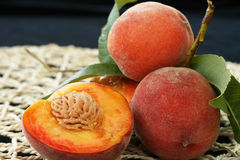 Fresh peaches with flesh and pit exposed. Sitting on straw mat Royalty Free Stock Photos