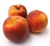 Fresh peaches isolated. Closeup of three fresh peaches isolated on white Stock Image