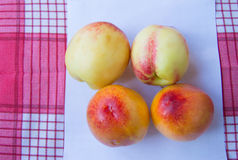 Fresh peaches nectarines on red checkered napkin, sheet of paper Royalty Free Stock Image
