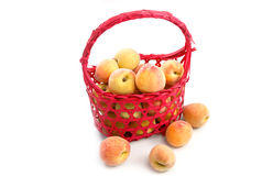 Fresh peaches in red basket isolate Stock Images