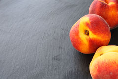 Fresh peaches on slate background Royalty Free Stock Photography
