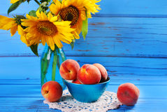 Fresh peaches and sunflowers Stock Images