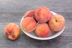 Fresh peaches in white bowl, on wooden background royalty free stock photos