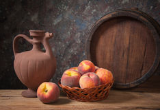 Fresh peaches in a wicker basket and her pitcher Stock Images