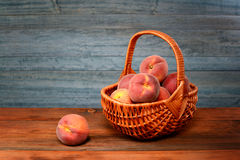 Fresh peaches in a wicker basket Stock Photo