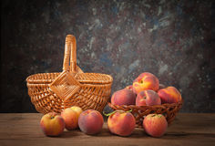 Fresh peaches and wicker basket Royalty Free Stock Images