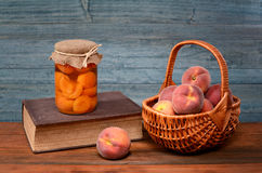 Fresh peaches in wicker baskets and books Royalty Free Stock Image