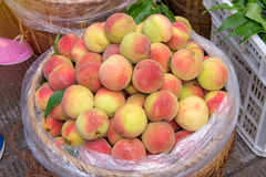 Fresh peaches in a wooden basket at the fruit market Stock Photo