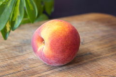Fresh peaches on a wooden cutting board. Royalty Free Stock Image