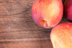 Fresh peaches on a wooden cutting board. Stock Photo