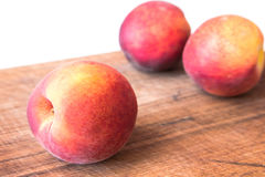 Fresh peaches on a wooden cutting board. Stock Photos