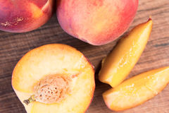 Fresh peaches on a wooden cutting board. Royalty Free Stock Photography