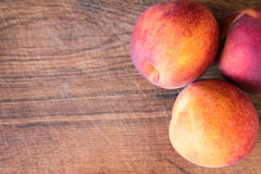 Fresh peaches on a wooden cutting board. Royalty Free Stock Images