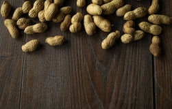 Fresh peanut butter on wooden ground. Some peanuts on a wooden brown table royalty free stock image