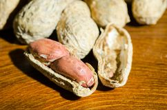 Fresh peanuts in shel and peeled without shell on the wooden table background close up.  Stock Images