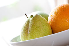 Fresh pear and an orange in white plate Stock Image
