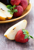 Fresh pear and strawberry on a wooden background Royalty Free Stock Photography
