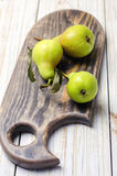 Fresh pears on brown wooden cutting board. Fresh green pears on brown wooden cutting board Royalty Free Stock Images