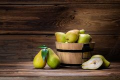 Fresh pears. With leaves in a basket on wooden background Royalty Free Stock Photos