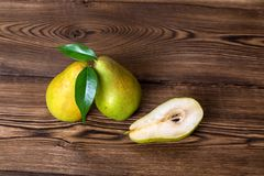 Fresh pears. With leaves in a basket on wooden background Stock Images