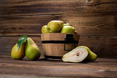 Fresh pears. With leaves in a basket on wooden background Royalty Free Stock Images