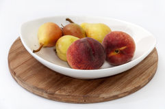 Fresh pears and peaches in a bowl Stock Photo