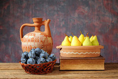 Fresh pears, plums and a ceramic carafe Royalty Free Stock Image