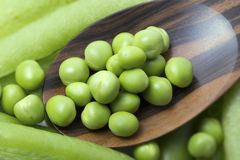Fresh peas on wooden spoon. With pods background Stock Photo