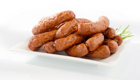 Fresh peasant sausage on a plate. Isolated on white background. Pork meat royalty free stock photo