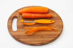 Fresh peeled carrots and peeling knife on a kitchen wooden board Stock Photos