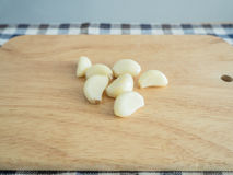 Fresh peeled garlic. Fresh peeled garlic on wooden kitchen block Stock Images