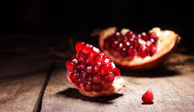 Fresh peeled pomegranates with ruby red beans on old wooden tabl Stock Images