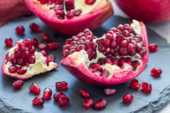 Fresh peeled red ripe pomegranate on gray slate board Stock Photo