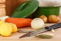 Fresh peeled vegetables, potatoes, carrots and onions on the cutting Board. With spices and knife Royalty Free Stock Photography