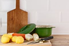 Fresh peeled vegetables, potatoes, carrots and onions on the cutting Board. With spices and knife. On white brick wall background Royalty Free Stock Image