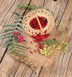 Fresh peppercorn and dried pink pepper scattered from  basket Royalty Free Stock Photography