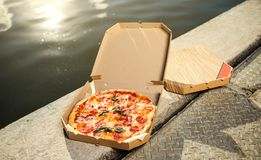 Fresh pepperoni pizza outdoor on the river. Food at the resort. Snack fastfood during vacation. Fresh pepperoni pizza outdoor on the river . Food at the resort royalty free stock images