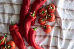 Fresh Peppers and Tomatoes On Cotton Cloth. Red tomatoes and peppers on stripped cloth Royalty Free Stock Photos